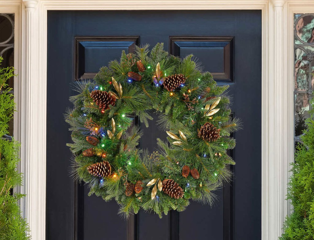 greenery wreath with pinecones, gold leaves, and multi-color lights on navy blue front door