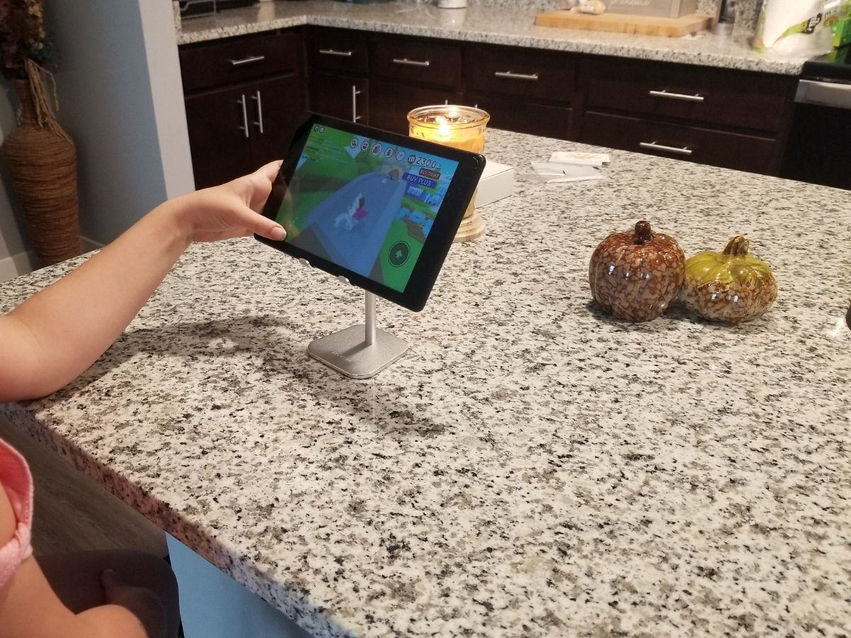 girl playing video game on ipad with phone stand holding ipad