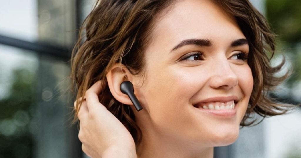 woman wearing black wireless earbuds outside