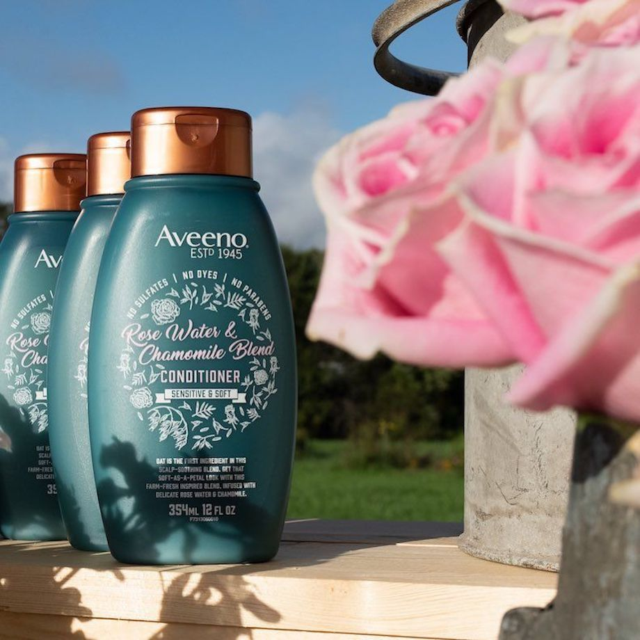Aveeno Rosewater Shampoos lined up next to roses