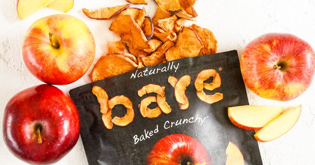 bag of bare baked apple chips with apple chips and red apples around it