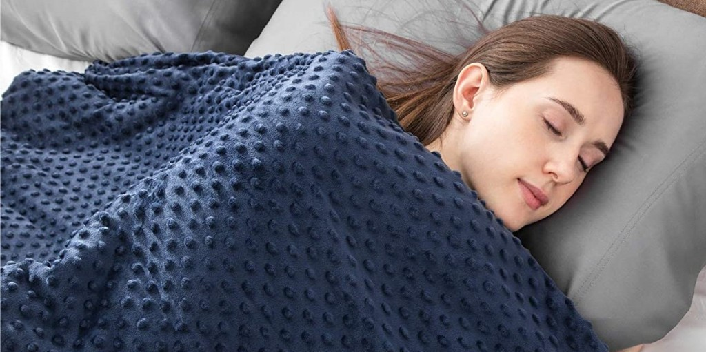 person laying with a weighted blanket
