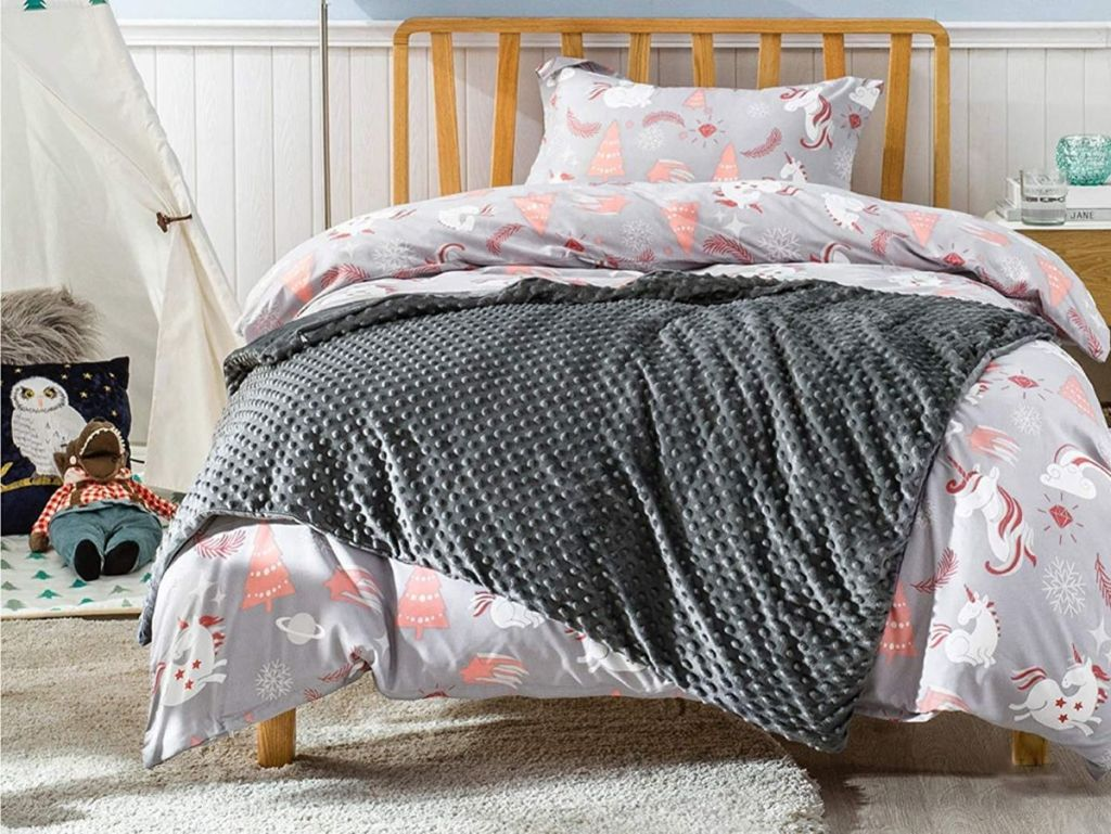 kids bedroom with unicorn quilt and grey blanket on bed