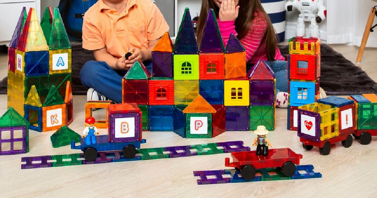 two kids and magnetic building tiles and toys on floor