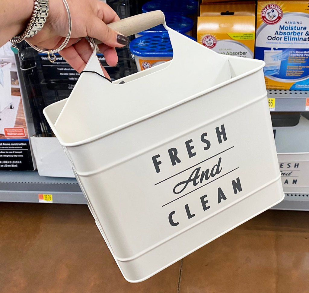 woman holding up white metal laundry caddy that says fresh and clean on the side