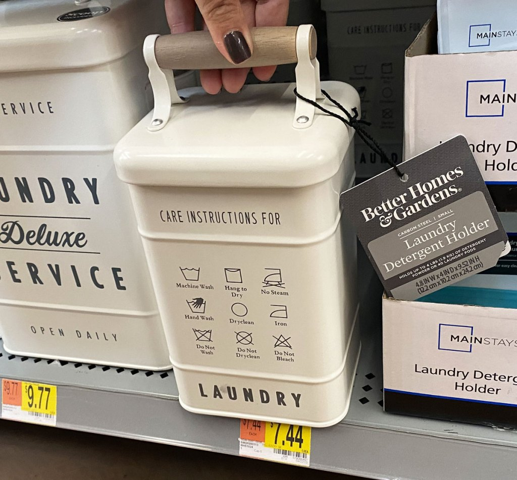 woman holding lid of a small metal laundry container on a walmart shelf