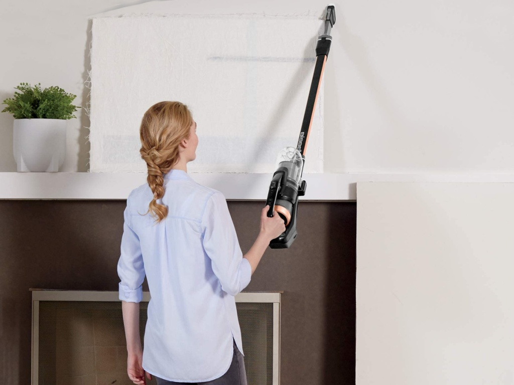 woman holding a handheld bissell vaccum cleaner in a living area up on the wall