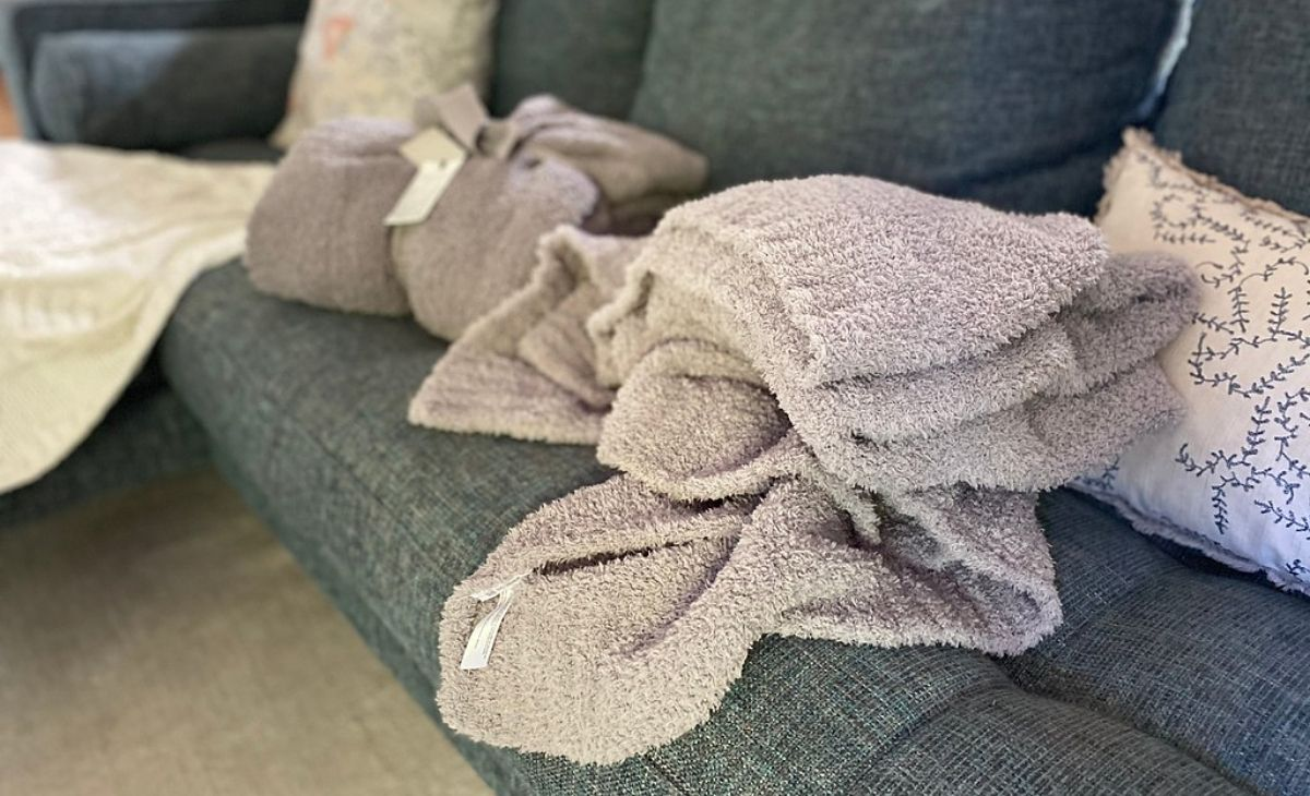 Gray barefoot dreams blanket and dupe blanket on a sofa