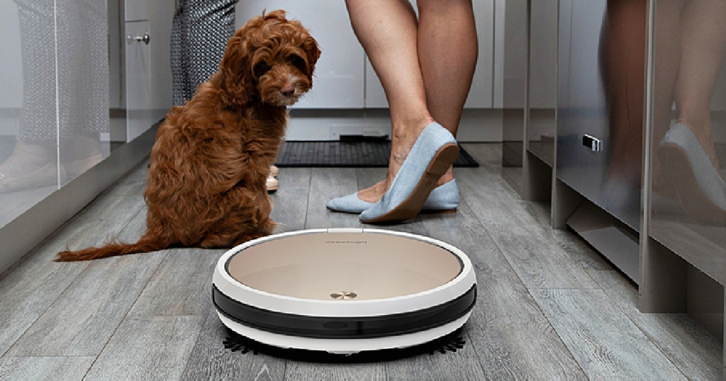 gold robotic vacuum on gray floor, dog, and two women