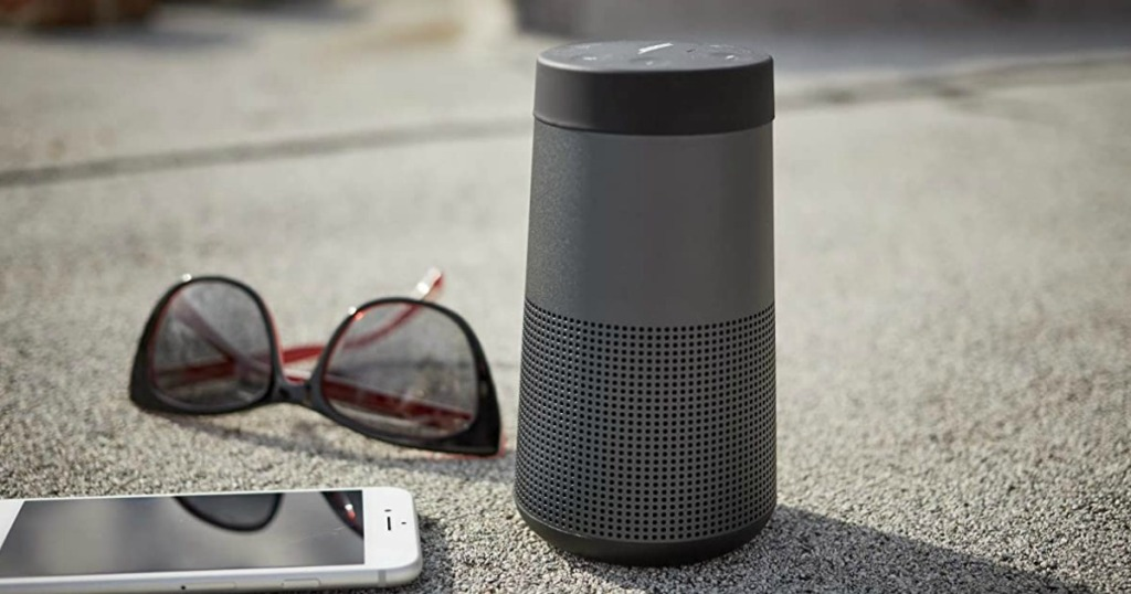 Large black speaker on a cement surface near phone and glasses
