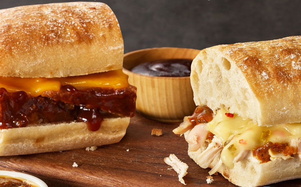 two boston market sandwich sliders on wood cutting board with dipping sauce