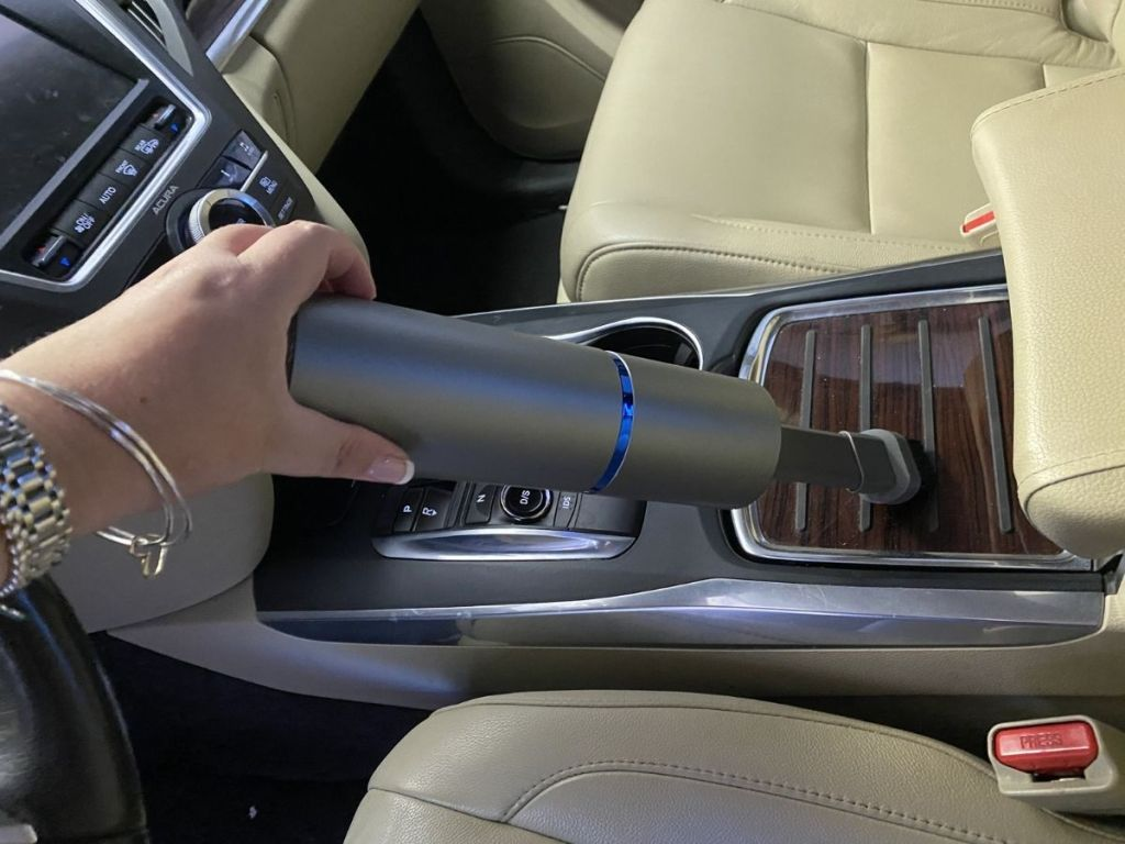 hand holding mini vacuum to clean center counsel in car