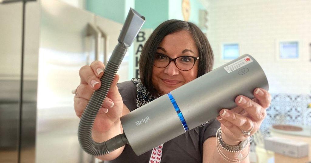 woman holding Brigii mini vacuum cleaner