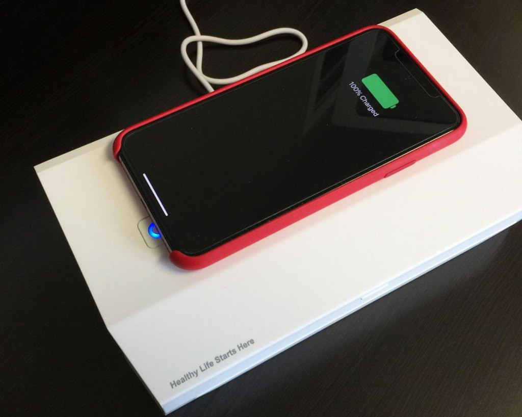 white uv sanitizing box with iphone wirelessly charging on top