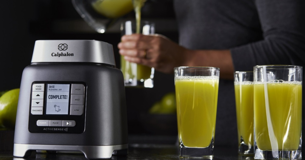 calphalon blender base sitting next to glasses with green liquid and person pouring juice in the background