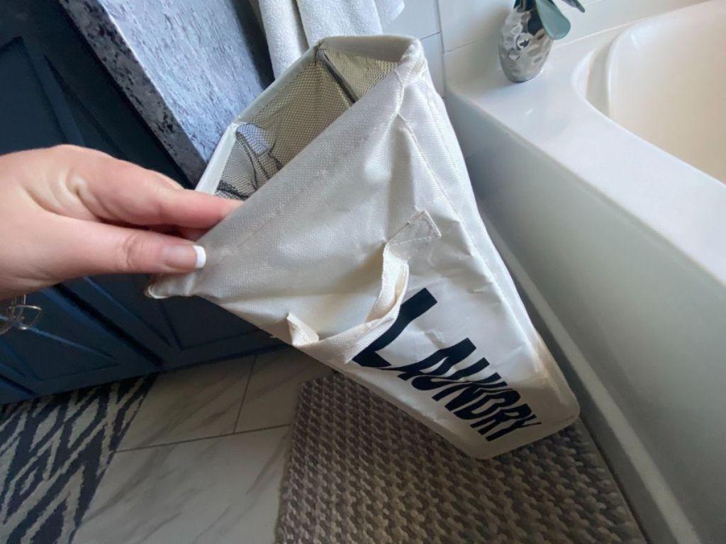 hand touching slim laundry bag next to bathtub
