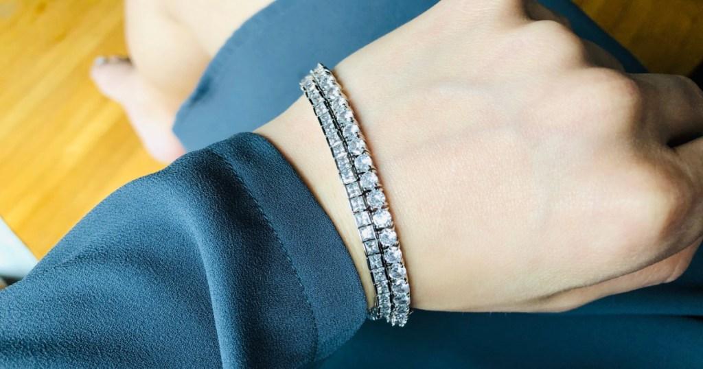two tennis bracelets on woman in blue dress