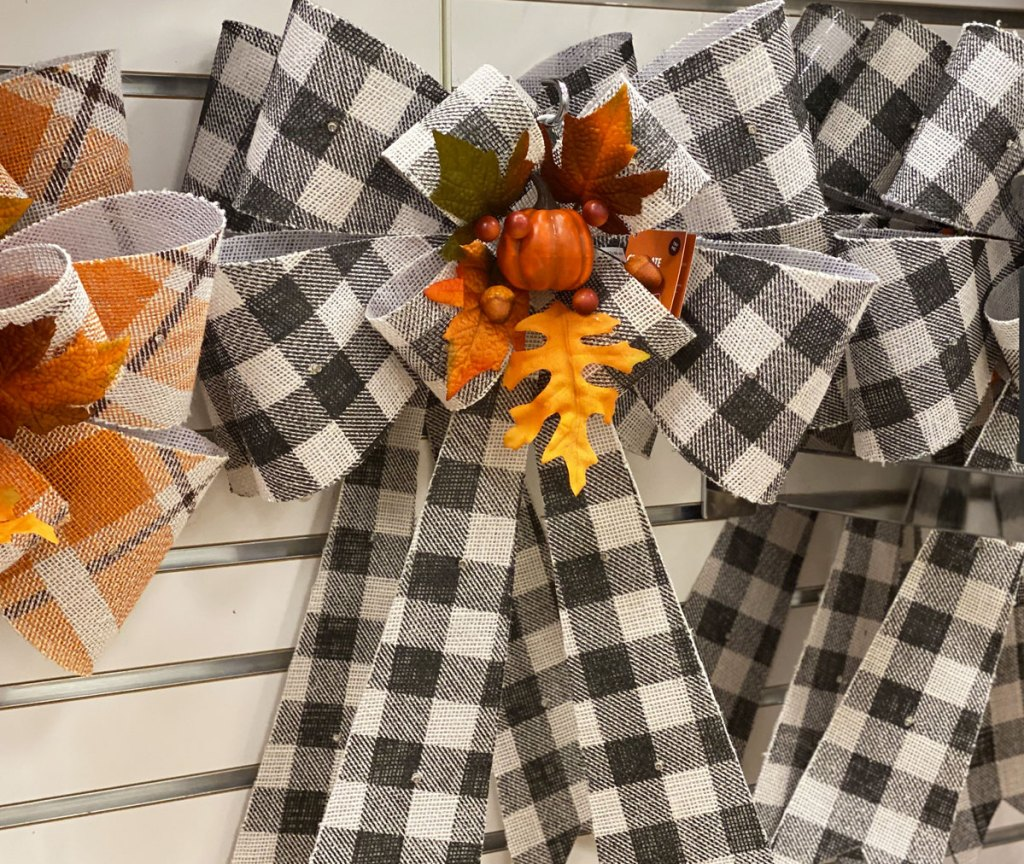 black and white buffalo check bow with led lights, pumpkin, and leaves in center of bow