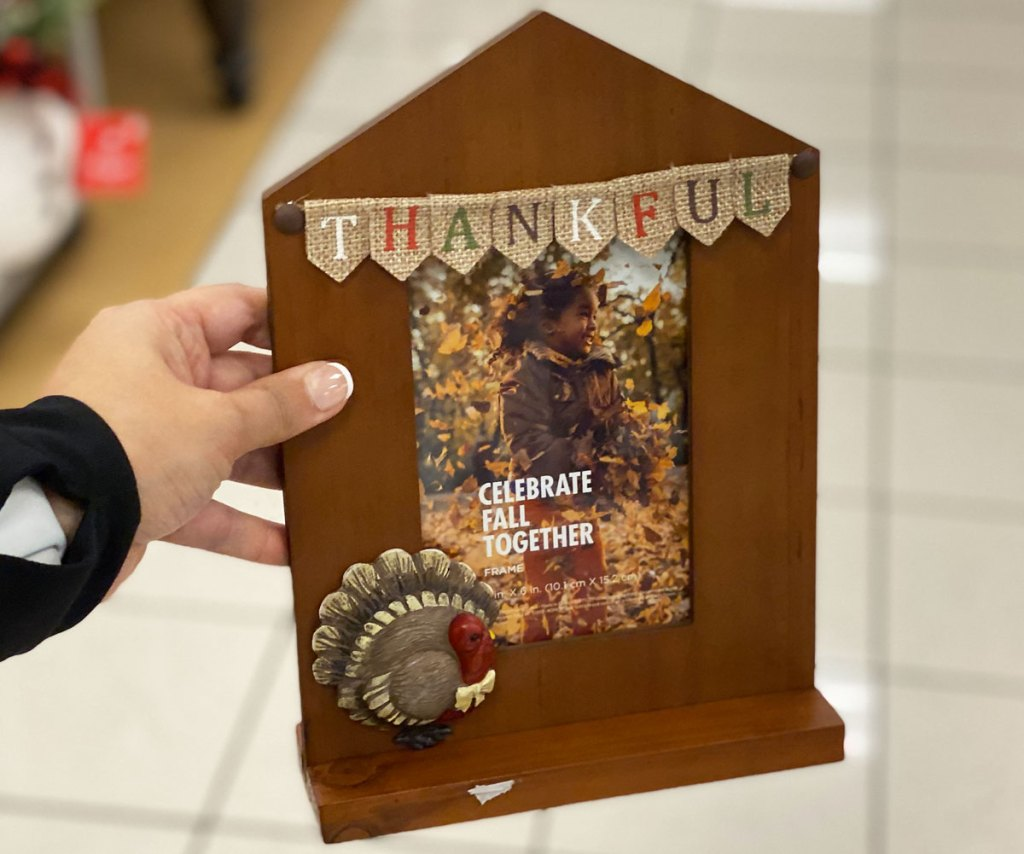 person holding up wood photo frame with turkey and banner that says thankful