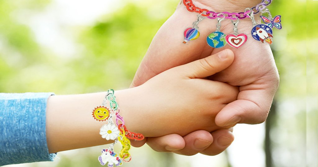 two kids holding hands with charm bracelets on their wrists