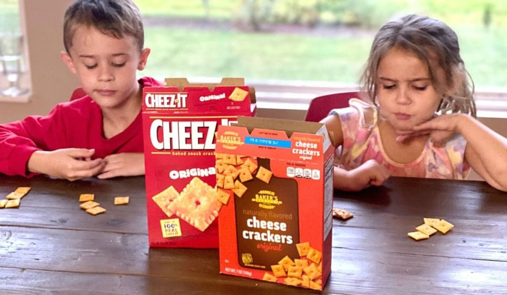 Two kids at a table with boxes of crackers
