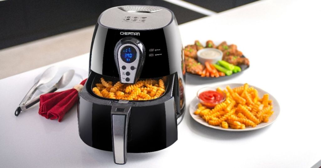 Chefman Digital Air Fryer 2.5L on counter with fries inside basket and food on counter top
