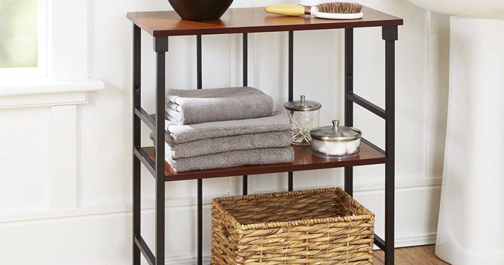 wood and metal three tier wall shelf on floor of bathroom with towels and storage basket on it