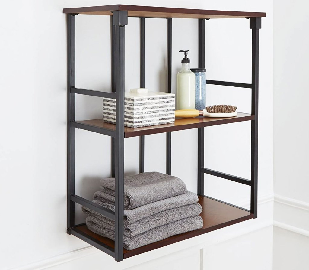 wood and metal three tier wall shelf on wall in bathroom with towels and lotion on it