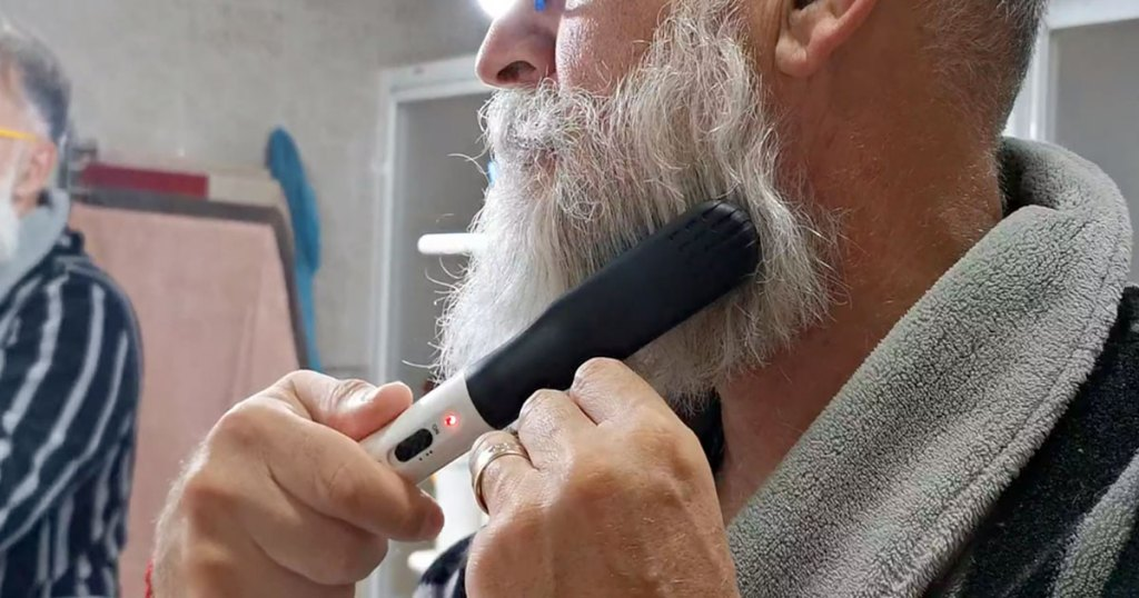 man using a beard straightening comb on his beard