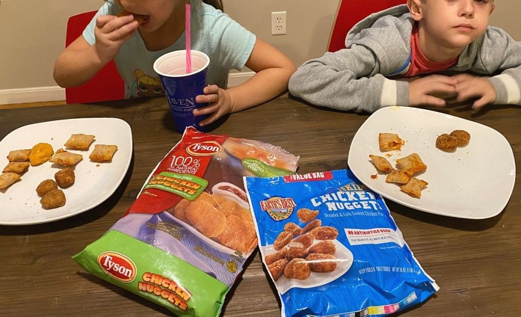Two kids tasting different chicken nugget brands at a table