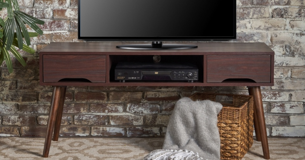 brown tv stand, tv, and bin with blanket