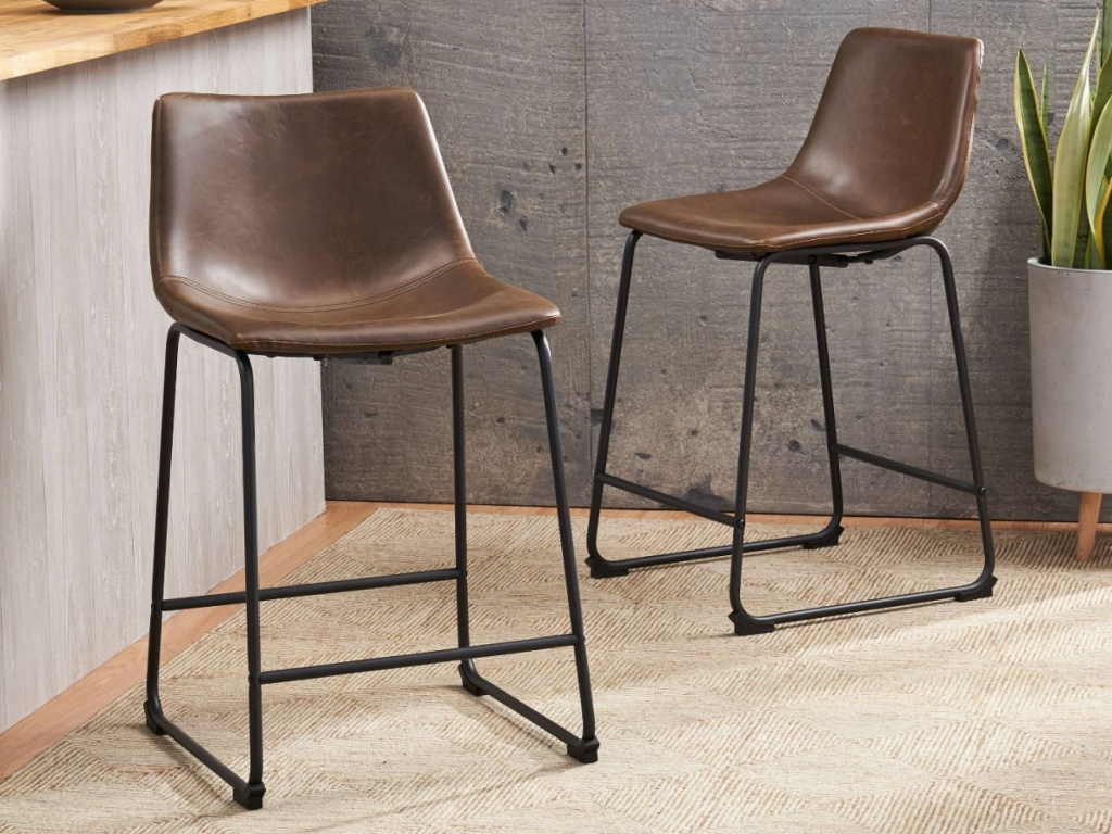two brown and black barstools in home