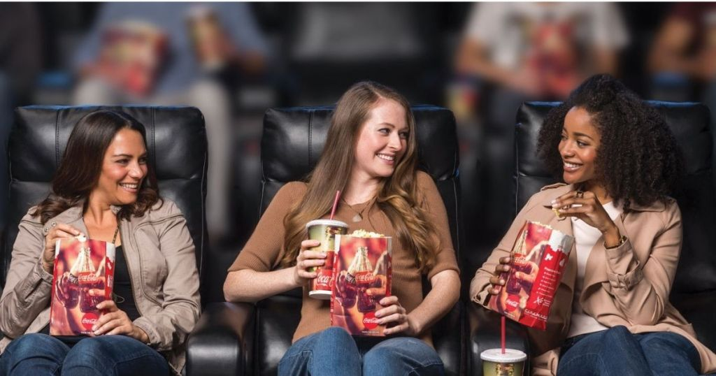 women sitting in theater with popcorn