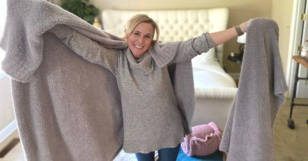 Seorang wanita dengan dua selimut besar di lengan
