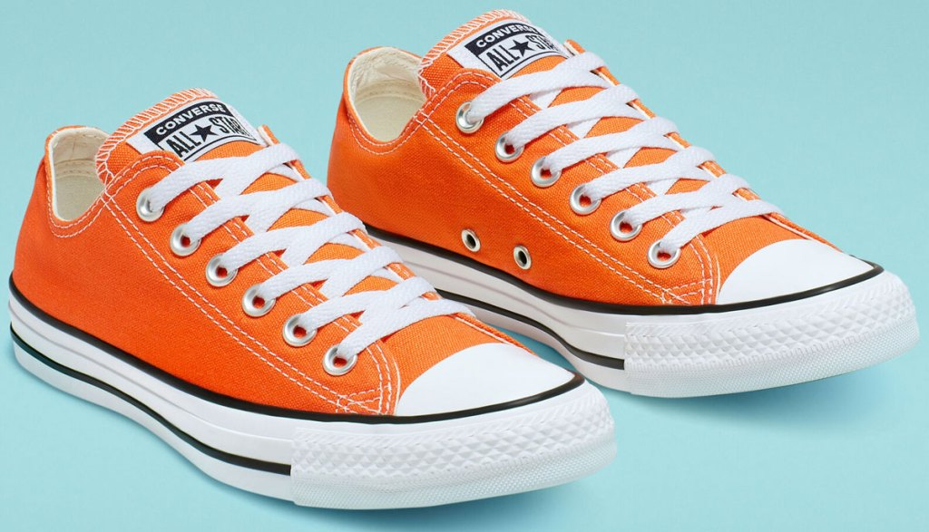 pair of bright orange converse low top shoes
