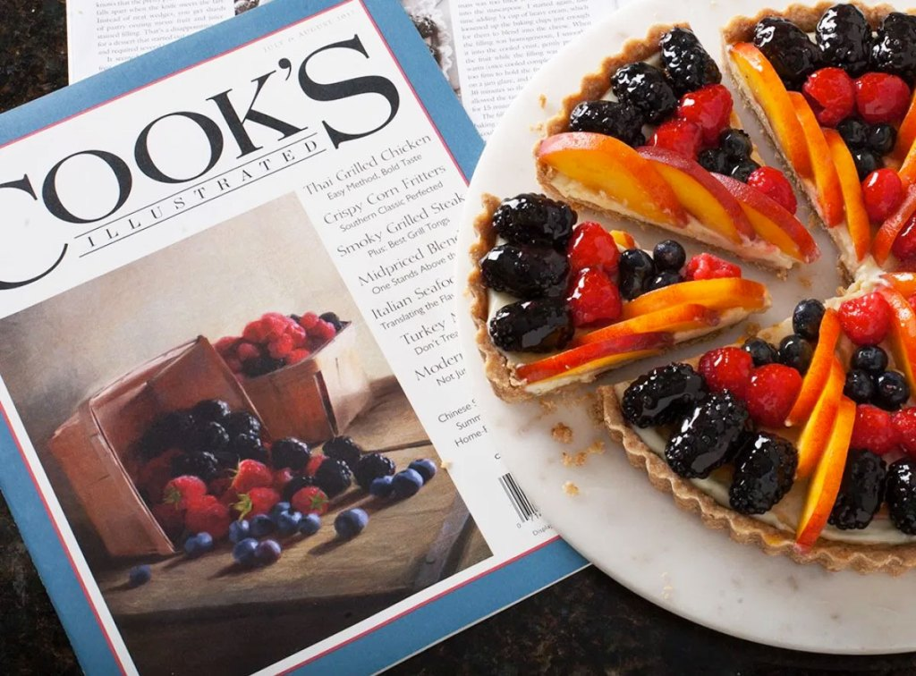 fruit tart on white plate on top of an issue of cooks illustrated magazine