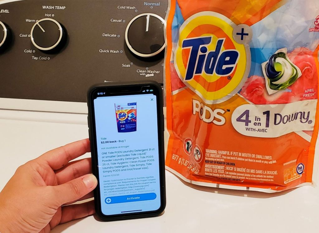 hand holding a phone next to a bag of Tide pods