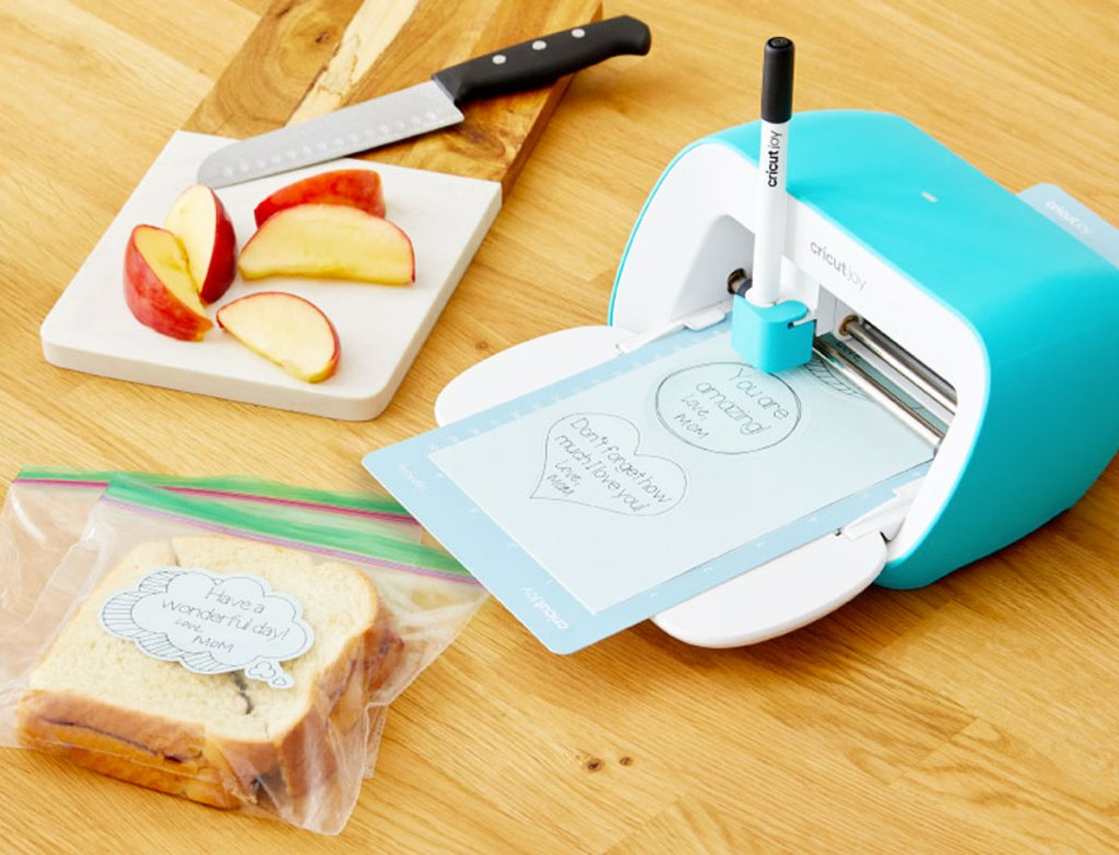 blue and white cricut joy machine printing stickers to go on packed lunches