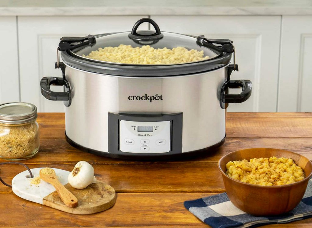 stainless steel crockpot on wood kitchen counter with mac & cheese inside it