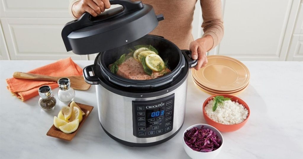 crock pot 6 qt on counter with food and lady lifting lid