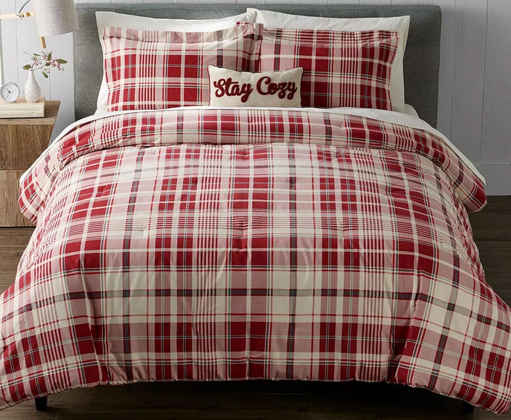 red and white plaid comforter set on bed with matching throw pillow that says stay cozy