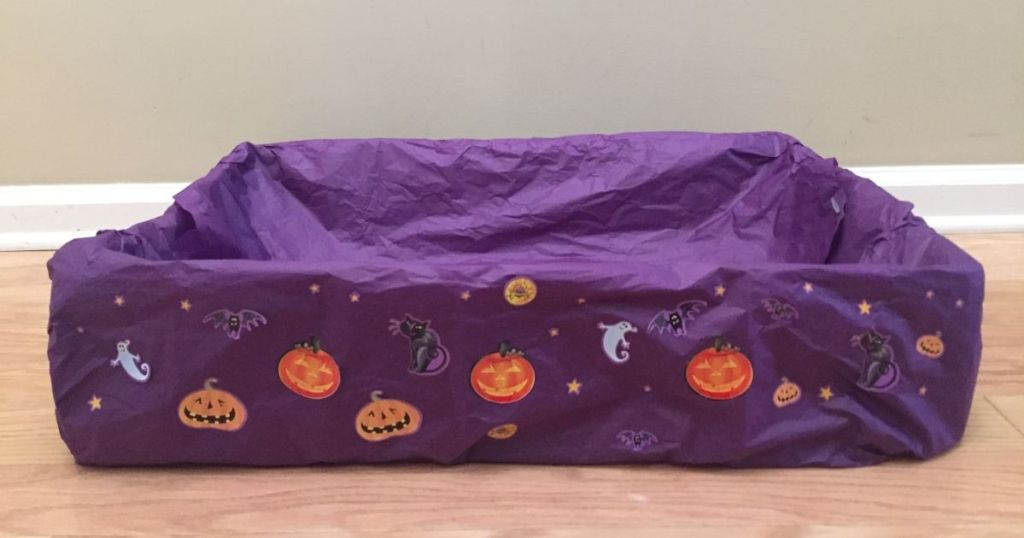 box covered with purple tissue paper and Halloween stickers