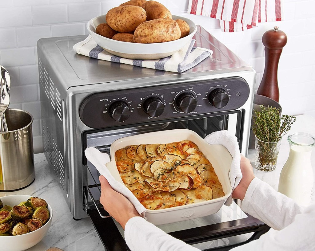 woman taking food out of an air fryer oven
