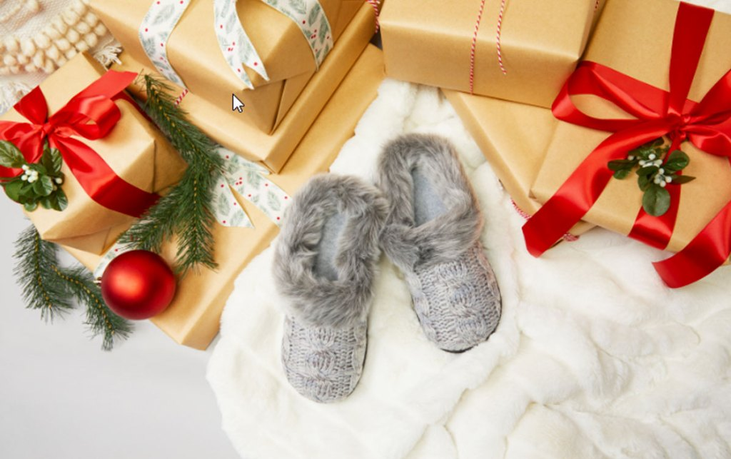 pair of grey cable knit slippers on fuzzy blanket next to christmas gifts