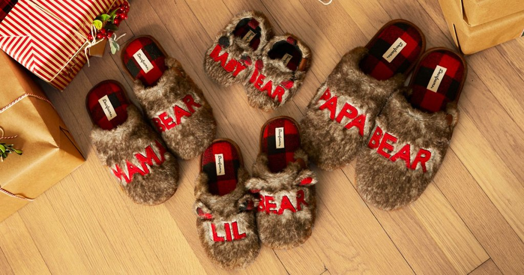 pairs of fuzzy brown matching family slippers on wood floor