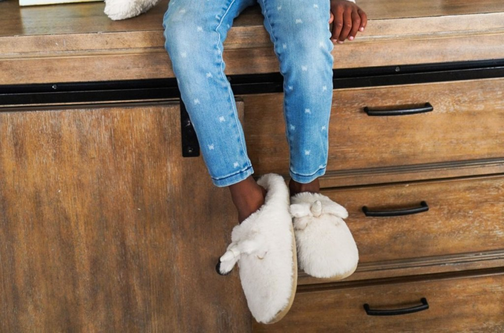 girl sitting on wood dresser wearing jeans and fuzzy unicorn slippers