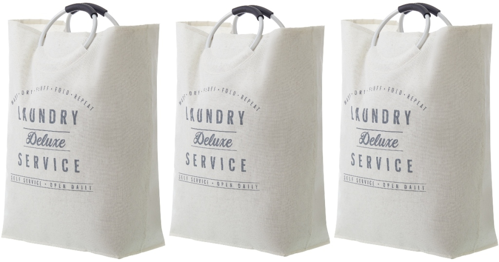 Three creamy white laundry totes that are farmhouse style with round metal handles