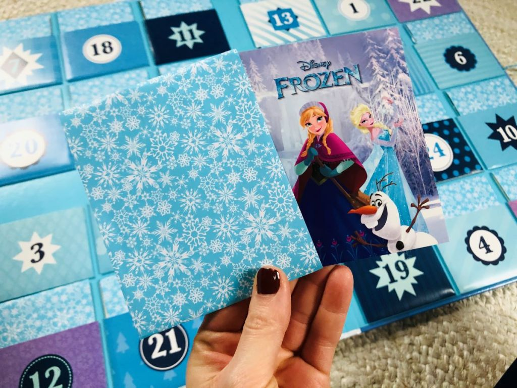 hand holding a Frozen storybook in front of an advent calendar