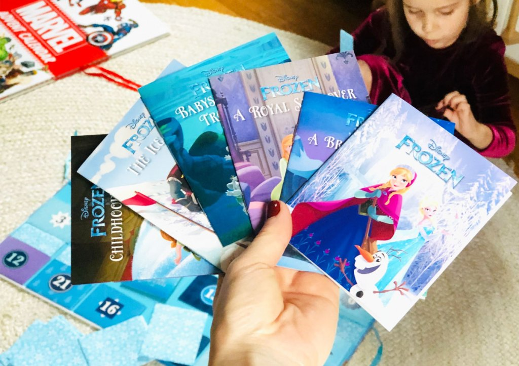 person holding up a variety of books that come inside the disney frozen storybook advent calendar