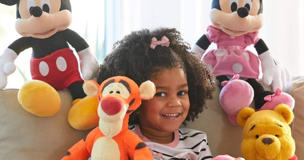 girl sitting on couch with four Disney plush toys